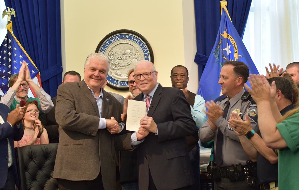 A Crowd of people applaud while two men in the center shake hands, while one displays a signed document